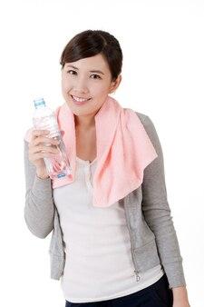 물, 흰색 바탕에 어깨에 수건으로 근접 촬영 초상화의 병을 들고 명랑 아시아 소녀.