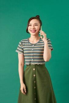 携帯電話で話している間笑っている陽気なアジアの女の子、