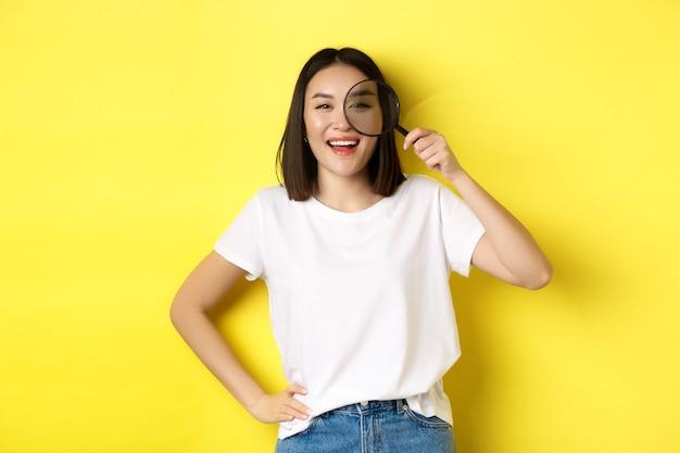 당신을 찾고, 돋보기를 통해보고 웃고 쾌활한 아시아 소녀는 노란색 배경 위에 서있는 흥미로운 것을 발견했습니다.
