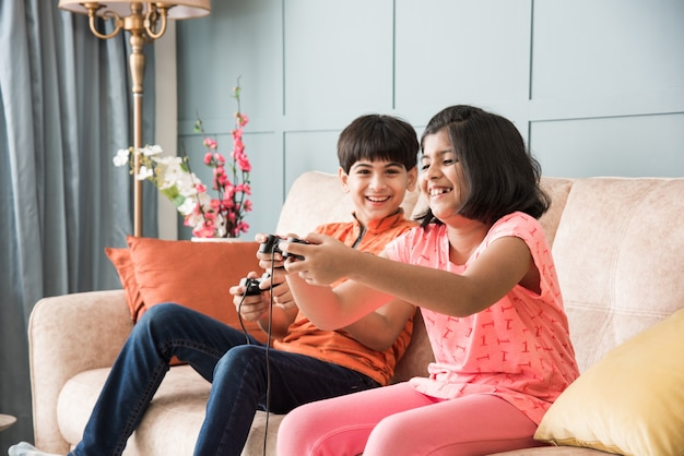 Cheerful asian indian kids playing video game using controller or joystick, sitting on sofa, couch