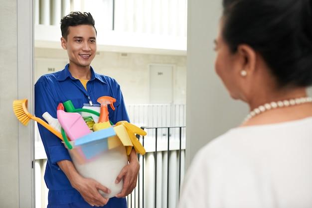 Веселый азиатский уборщик с инструментами стоит у двери и разговаривает с состоятельной женщиной-домовладельцем
