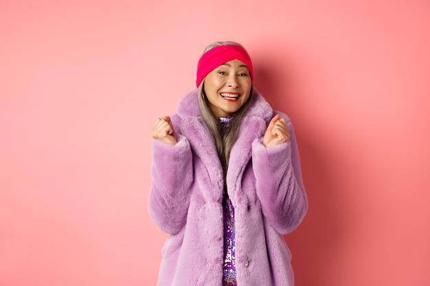 スタイリッシュなファンキーなコートを着た陽気なアジアの女性、勝利または成功を祝って、はいと言って幸せな笑顔、ピンクの背景の上に立って