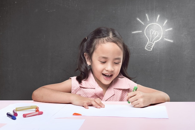 Cheerful asian little girl having new idea for drawing with crayon