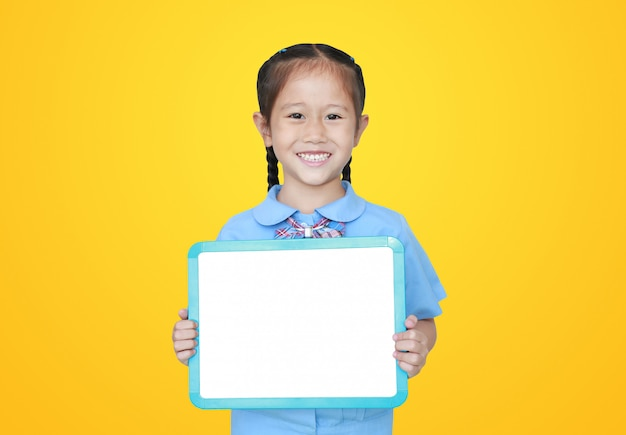 Cheerful asian little girl in school uniform holding blank white blackboard isolated . student and education concept.