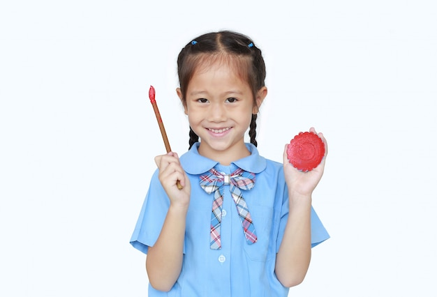 Cheerful asian little girl in school uniform holding red dipped paintbrush and palette
