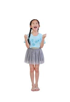 Веселая азиатская маленькая девочка с косичками стоит и поднимает руки вверх изолированной на белой стене