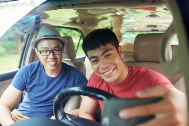 Cheerful asian male friends sitting together in car and taking selfie