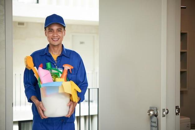 Cheerful asian male janitor walking into hotel room, carrying supplies in bucket