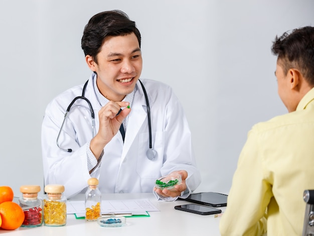 Cheerful asian male physician and patient sitting at table and talking about pills while looking at each other during appointment on white background