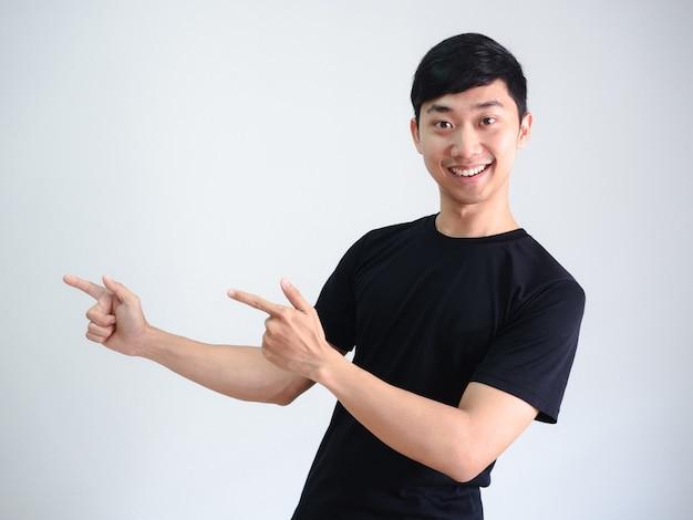 Веселый азиатский мужчина указывает двойной палец на левой стороне портрета на фоне белой стены