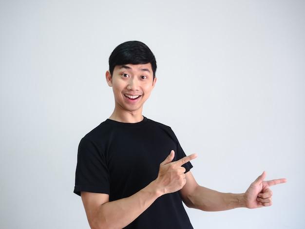 Веселый азиатский мужчина указывает двойной палец на правой стороне портрета на фоне белой стены