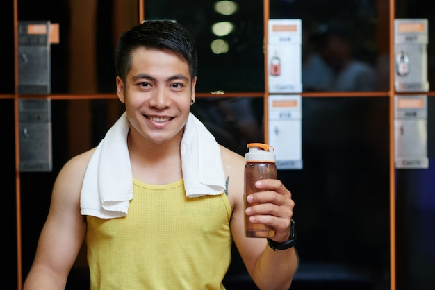 Cheerful asian man posing in locker room in gym with sports bottle
