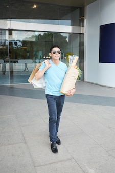 Cheerful asian man posing with shopping bags and groceries at building entrance