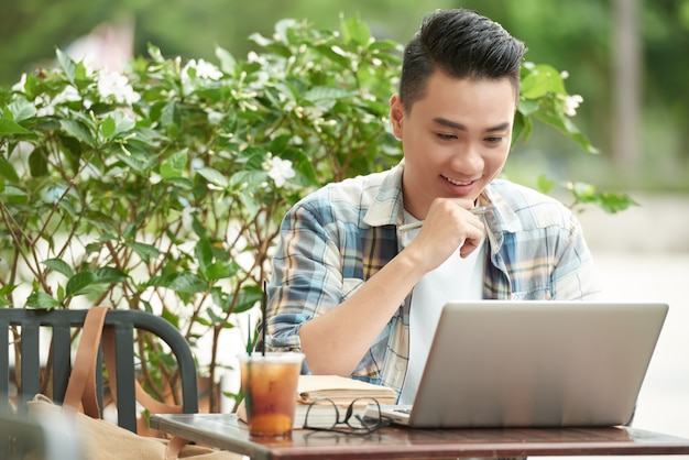 Cheerful asian man sitting at outdoor cafe and looking at laptop screen with excitement