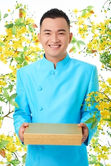 Cheerful asian man in traditional turquoise jacket standing against blooming mimosa and holding box