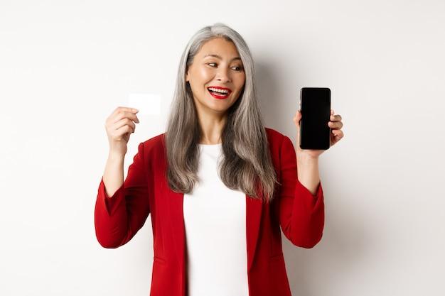 빈 스마트폰 화면과 신용 카드, 전자 상거래의 개념을 보여주는 쾌활한 아시아 성숙한 여성.