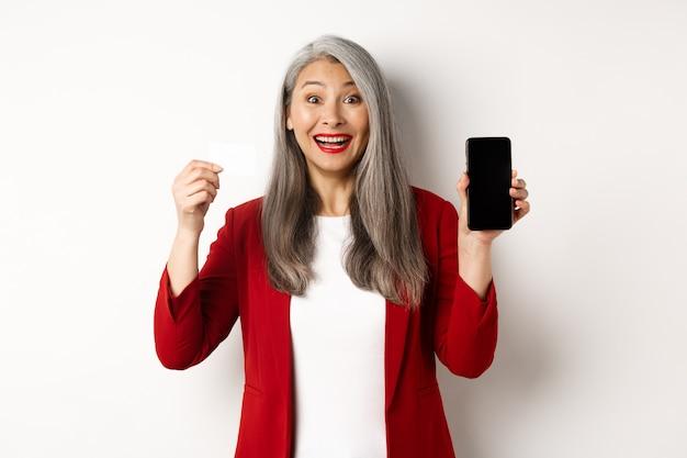 Donna matura asiatica allegra che mostra lo schermo in bianco dello smartphone e la carta di credito, il concetto di commercio elettronico.