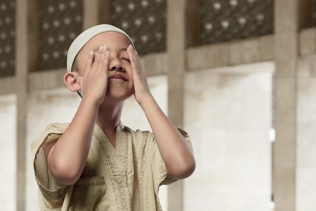 Cheerful asian muslim child praying to god