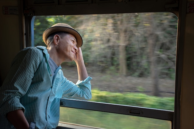 Cheerful asian passenger wearing hat looking out of train window