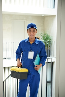 Cheerful asian plumber in overalls standing at door with toolbox