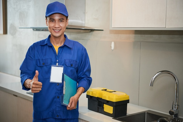 Cheerful asian plumber standing near kitchen sink and showing thumb up