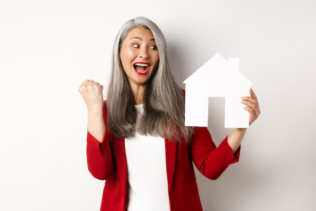 Cheerful asian senior woman buying house, scream of joy and making fist pump while showing paper house cutout, standing over white background.