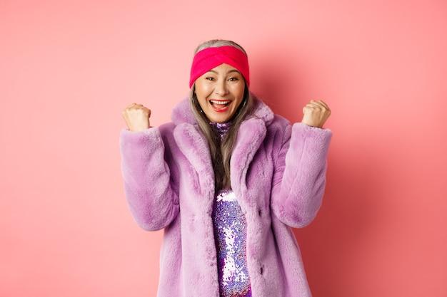 陽気なアジアの年配の女性が賞を受賞し、祝っています。ピンクの背景の上に立って、イエスと言って、勝利で拳を握り締める古いファンキーな女性