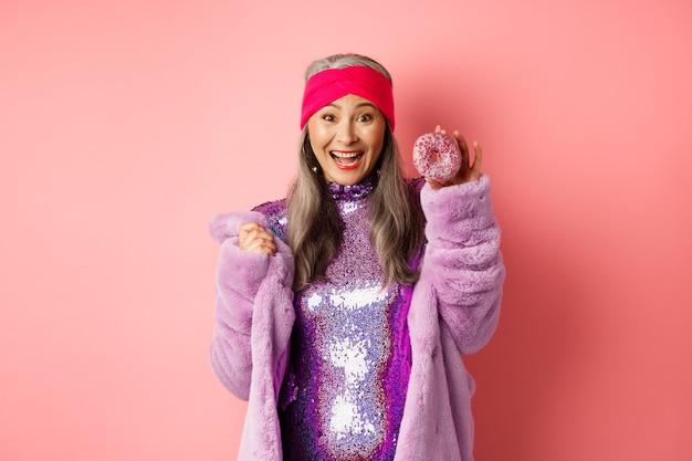 회색 머리를 한 쾌활한 아시아 노인 여성, 파티용 반짝이 드레스를 입고 맛있는 도넛을 보여주고 행복하게 웃고, 달콤한 음식을 먹고, 분홍색 배경 위에 서 있습니다.