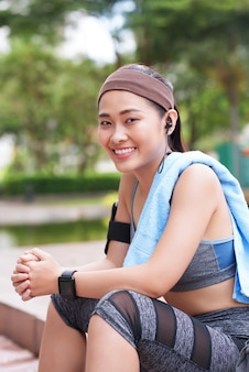 Cheerful asian sportswoman sitting in park