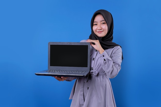 Cheerful asian woman bring a laptop using her hand