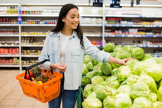 Cheerful asian woman choosing cabbage in market
