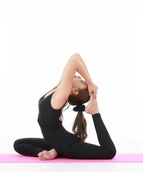 Cheerful asian woman concentrate on body arrangement while doing eka pada rajakapotasana pose