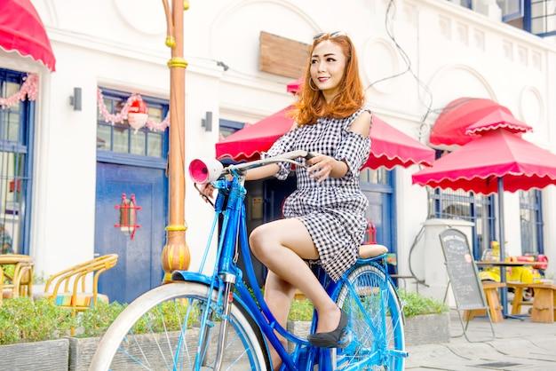 Cheerful asian woman cycling