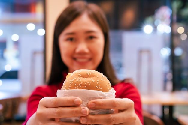 陽気なアジアの女性は夜にファーストフードレストランで焼き肉ハンバーガーを食べることをお楽しみください