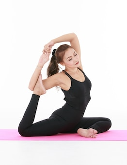 Cheerful asian woman focusing and concentrate on body arrangement while doing eka pada rajakapotasana pose during yoga session against white background