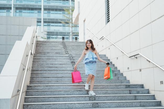 カラフルなショップ パッケージで階段を降りる陽気なアジアの女性。ショッピングとファッションのコンセプト