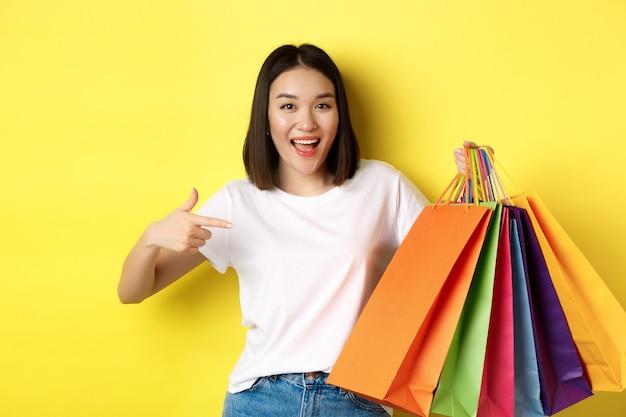 買い物に行く陽気なアジアの女性、紙袋に人差し指と笑顔、割引中に楽しんでいる買い物客、黄色の背景。