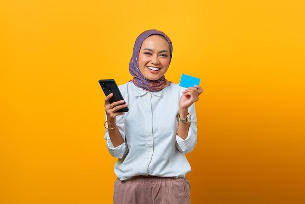 スマートフォンを保持し、黄色の背景の上に空白のカードを表示して陽気なアジアの女性