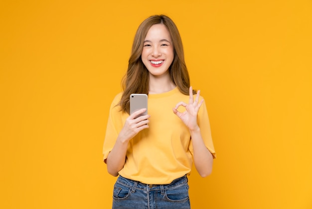 Cheerful asian woman holding smartphone and shows ok sign on light yellow background.