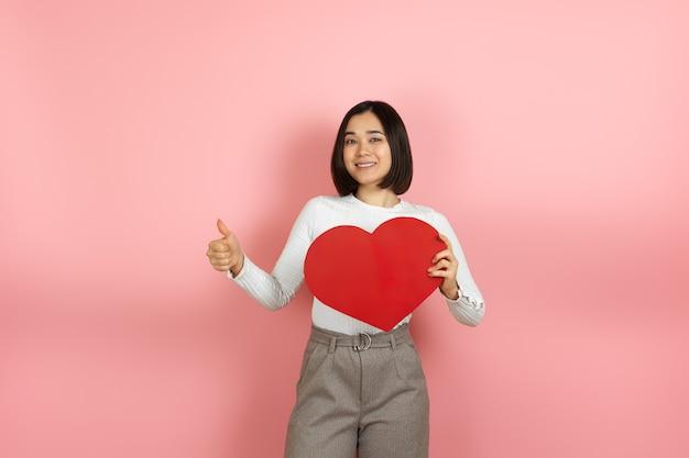 Веселая азиатка держит в руках большое красное бумажное сердце и показывает палец вверх