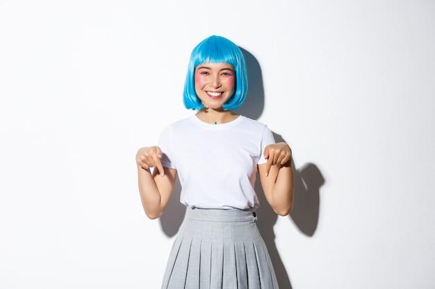 쾌활한 아시아 여자 애니메이션 스타일 복장, 파란색 가발을 착용하고 행복하게 웃고, 손가락을 아래로 가리키고, 광고를 표시하고, 서.