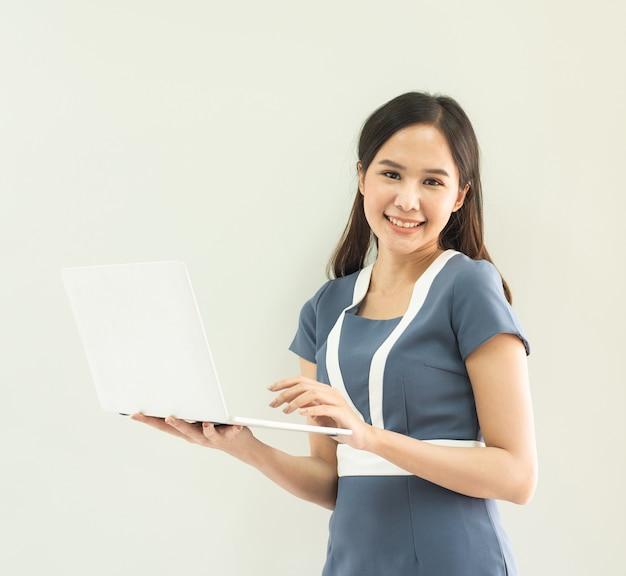 회색 벽에 고립 된 노트북을 들고 아름 다운 정장 서 손에 쾌활 한 아시아 여자.