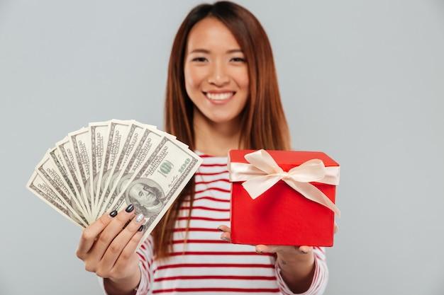 회색 배경 위에 카메라에 돈과 선물을 제시하는 스웨터에 쾌활 한 아시아 여자