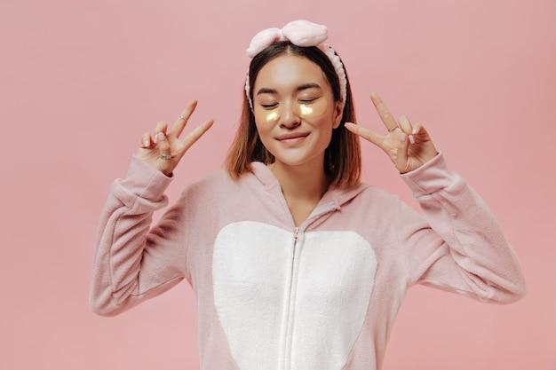 Una donna asiatica allegra in kigurumi e fascia per la testa mostra segni di pace e posa con gli occhi chiusi sul muro rosa