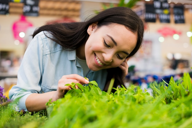 Cheerful asian woman smelling greenery in grocery store