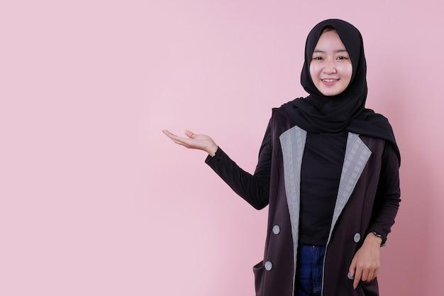 Веселая азиатская женщина улыбается и показывает что-то руками