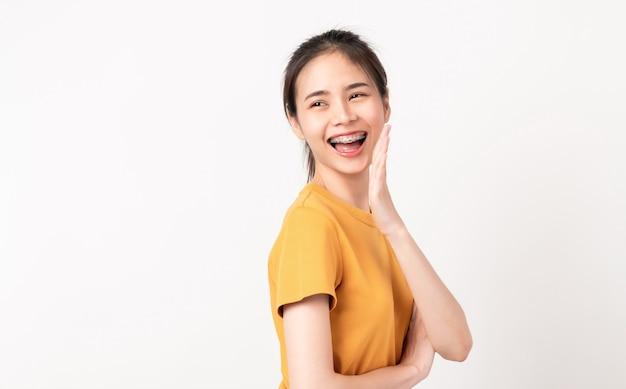 Веселая азиатская женщина стоит и объявляет руками ко рту и рассказывает секрет
