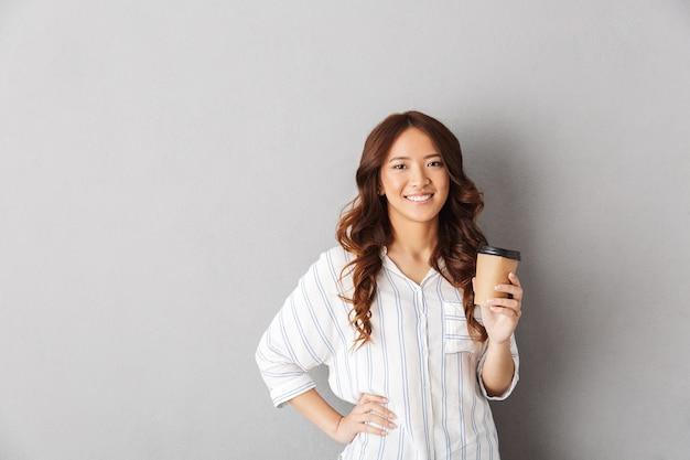 Cheerful asian woman standing isolated, drinking coffee