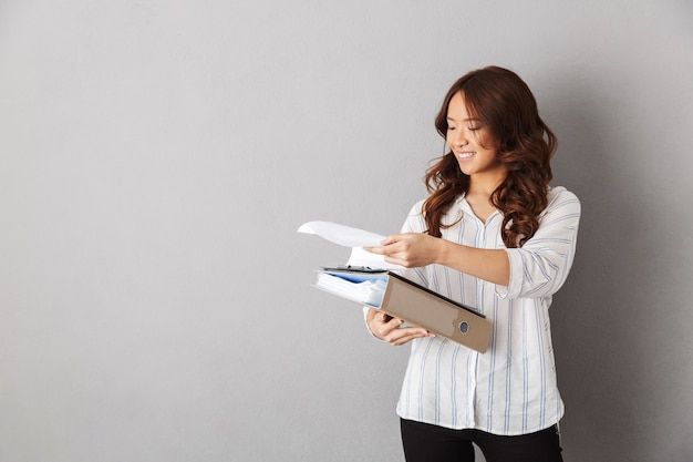 Cheerful asian woman standing isolated, holding folders