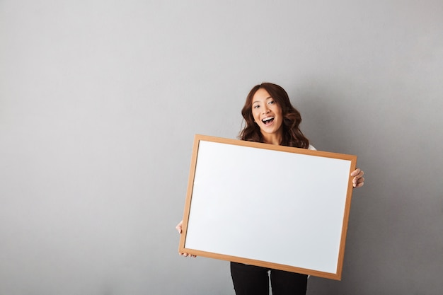 Cheerful asian woman standing isolated, showing blank board